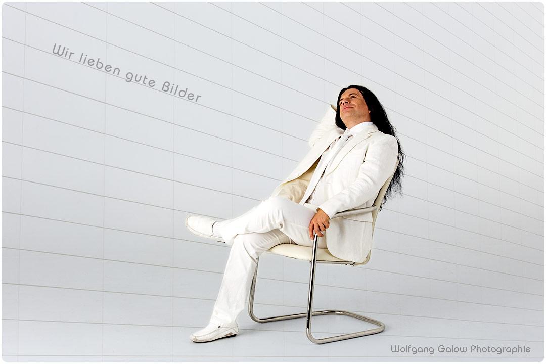 Foto im Querformat: In diesem Foto sitzt ei Mann in hellem Anzug und mit langen dunklen Haaren lässig in einem freischwingenden Stuhl, die rechte Hand nachdenklich an der Schläfe, nach vorne oben blickend. Im Hintergrund erkennt man zart die Linien einer hellen Mauer, die von links oben nach rechts unten zu fliehen scheinen (Fotograf München)