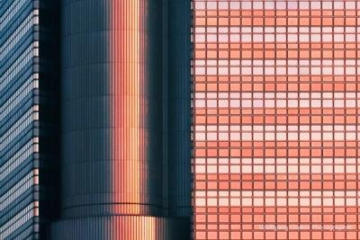 Foto im Querformat: Die schräg stehende Sonne scheint auf die Glaswand-Front der Hypobank und im roten Licht und im Schatten ums Eck liegt alles in tiefem Blau des Himmelslichtes