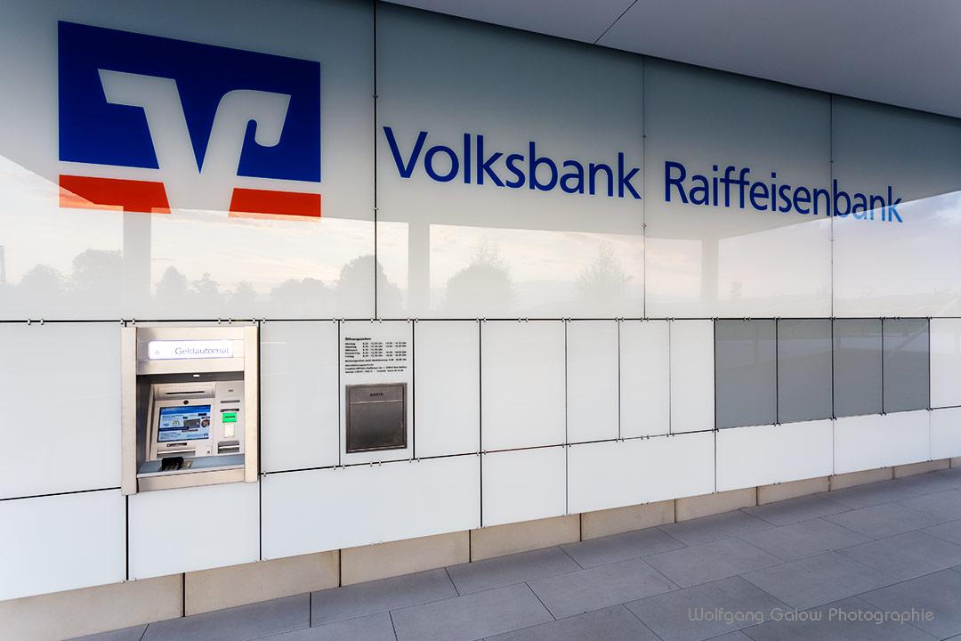 Foto im Querformat: Architekturfotografie: Das moderne Gebäude der Raiffeisenbank Bad Aibling - in den emaillierten Glassplatten, die das Gebäude vollständig verkleiden, spiegelt sich der blauweiße Himmel