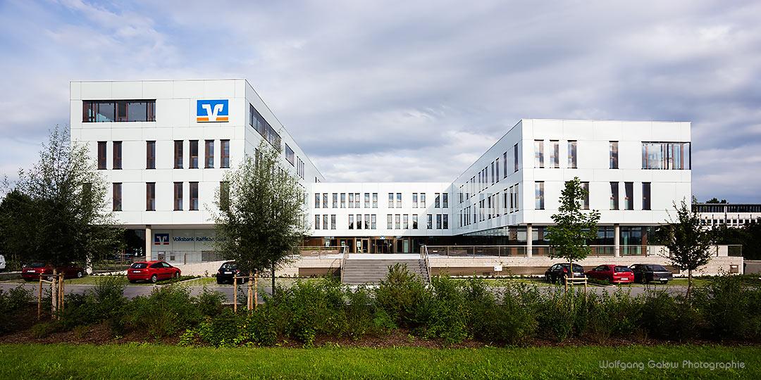 Foto im PAnorama-Querformat: Die VR-Bank Bad Aibling - Vollständiges Gebäude mit Grün im Vordergrund