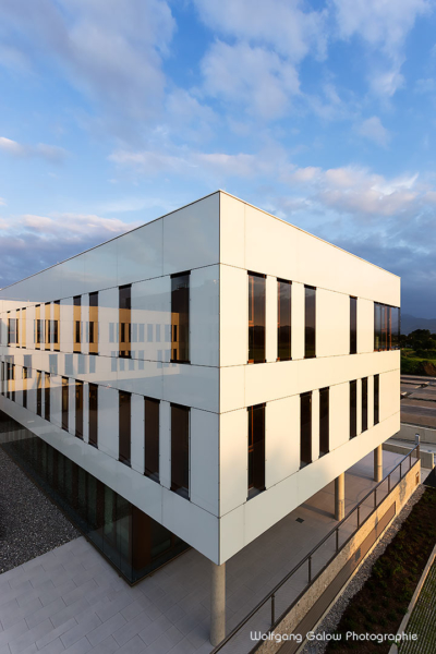 Foto im Hochformat: in den emaillierten Glasplatten, die die VR-Bank Bad Aibling verkleiden, spiegeln sich Himmel und Wolken