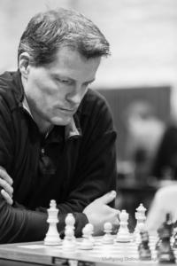 Foto (Schwarz-Weiß) im Hochformat: Großmeister Bezold mit verschränkten Armen am Schachbrett, den Blick konzentriert auf die Stellung gerichtet
