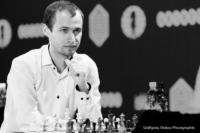 Foto (Schwarz-Weiß) im Querformat: Großmeister Zhigalko fixiert mit einem eindringlichen Blick seinen Gegner
