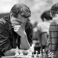 Foto (Schwarz-Weiß) im Quadrat: Großmeister Michael Bezold in nachdenklicher Position, den Kopf auf die Hand gestützt