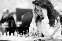 Foto (Schwarz-Weiß) im Querformat: die Damen-Großmeisterin hat den Kopf zum Nachdenken in beide Hände gestützt