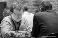 Foto (Schwarz-Weiß) im Querformat: ein Schachspieler mit Brille, mit verschränkten Armen auf dem Tisch vor dem Brett, den Blick konzentriert auf die Figuren gerichtet