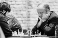 Foto (Schwarz-Weiß) im Querformat: ein Schachspieler, das Gesicht tief in die Hände vergraben, die Ellbogen auf den Tisch aufgestellt
