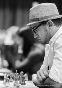 Foto (Schwarz-Weiß) im Hochformat: ein Spieler mit hellem Hut und dunkler Brille konzentriert sich auf das Brett