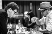 Foto (Schwarz-Weiß) im Hochformat: die Hand des Spielers mit Hut schwebt über dem Brett