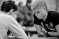Foto (Schwarz-Weiß) im Querformat: ein junger Spieler hat den Oberkörper weit über das Brett gebeugt