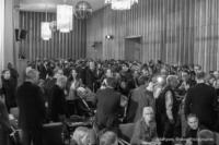 Foto (Schwarz-Weiß) im Querformat: Alle Gäste sitzen und stehen eng im Vorraum des Kinos