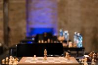 Foto (Color) im Querformat: im Vordergrund ein hellbeleuchtetes, fast leeres Schachbrett