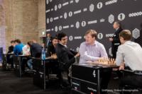 Foto (Color) im Querformat: zwei Spieler auf der Toptribüne, die Rücken an Rücken sitzen, plaudern kurz vor Rundenbeginn miteinander