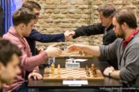 Foto (Color) im Querformat: die Spieler sitzen einander gegenüber und geben sich die Hand