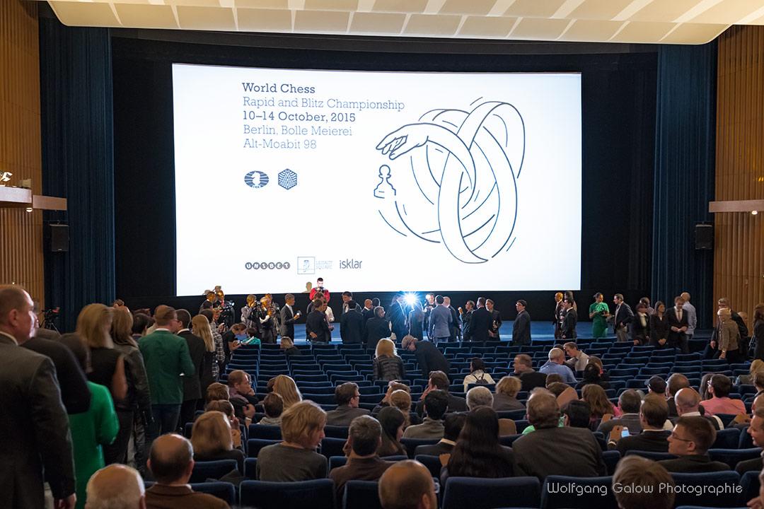 Im Kinosaal: die Leinwand zeigt das Signet der Schnellschachweltmeisterschaft. Im Vordergrund sitzen die Zuschauer und Teilnehmer und der Präsident des Weltschachbundes FIDE hält die Eröffnungsrede.