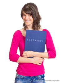 Bewerbungsfoto und Portrait im Hochformat, weiblich, im Fotostudio vor blauem hellem Hintergrund
