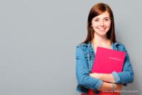 Bewerbungsfoto und Portrait im Querformat, weiblich, im Fotostudio vor mittelgrauem Hintergrund