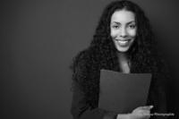 Bewerbungsfoto und Portrait im Querformat, weiblich, im Fotostudio vor dunkelgrauem Hintergrund