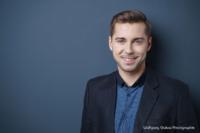 Bewerbungsfoto und Portrait im Querformat, männlich, im Fotostudio vor blauem dunkelblauem Hintergrund