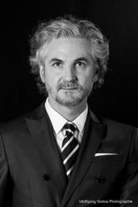 Bewerbungsfoto und Portrait im Hochformat, männlich, im Fotostudio vor dunklem Hintergrund