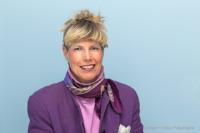 Bewerbungsfoto und Portrait im Querformat, weiblich, im Fotostudio vor blaugrauem Hintergrund