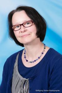 Bewerbungsfoto und Portrait im Hochformat, weiblich, im Fotostudio vor blauem Verlaufs-Hintergrund