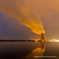 Farbfoto im quadratischen Format: Nachtaufnahme mit Langzeitbelichtung der Kühlturm mit den schräg aufsteigenden Kühlungsdunst in gelb-orangem Licht