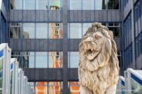 In der Fensterfassade der bayerischen Landesbank spiegelt sich eine Kirche. Im Vordergrund eine steinerne Löwenstatue.